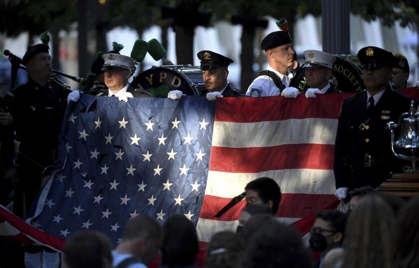 Policías y bomberos de Nueva York sostienen una bandera estadounidense mientras una banda