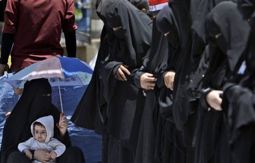 A female anti-government protestor, bottom left, shelters her son from the sun under an umbrella, while others pray during a demonstration demanding the resignation of Yemeni President Ali Abdullah Saleh, in Sanaa, Yemen, Sunday, April 3, 2011. Yemen's political opposition on Saturday presented the most detailed outline of how it hopes to see power change hands after nearly two months of protests that have weakened the longtime president but failed to drive him from office. (AP Photo/Muhammed Muheisen)