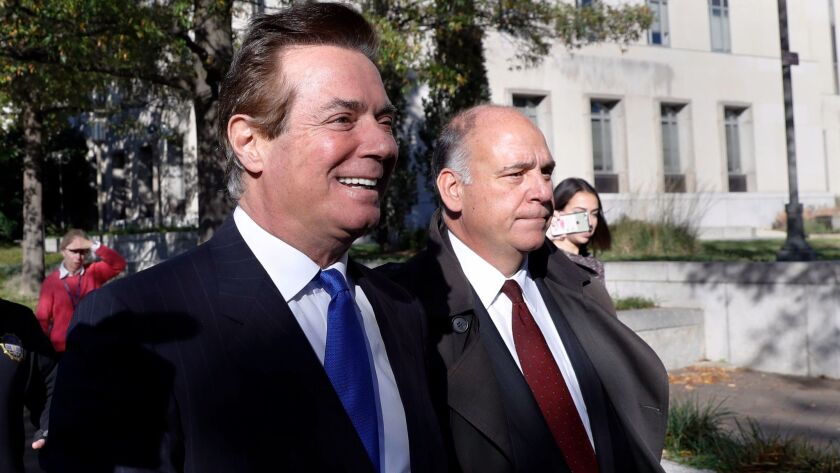 Former Trump campaign manager Paul Manafort, left, leaves Federal District Court in Washington on Oct. 30.
