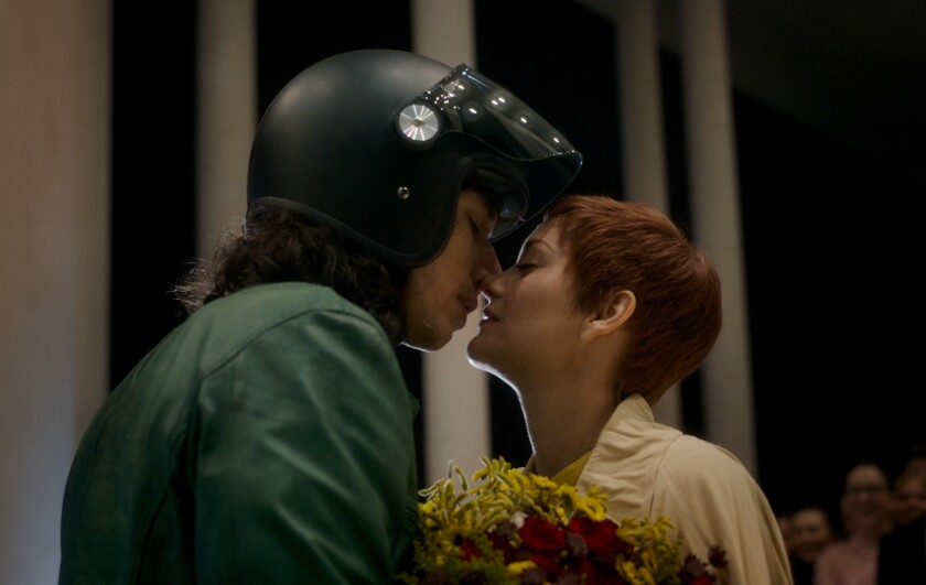 A man wearing a motorcycle helmet and a woman with short hear are about to kiss.