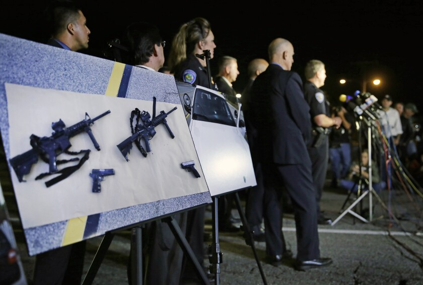 Police photos of assault rifles and handguns are displayed during a news conference