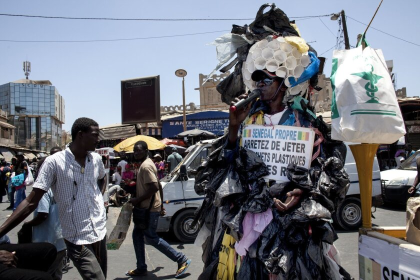 In this photo taken on Thursday, May 28, 2015, Modou Fall, right, clad  in more than 7,000 thin plastic sacks and a dome cap made from 100 plastic cups stapled together, speaks on a microphone as he tries to get Senegalese to stop littering and quit using plastic bags, in Dakar, Senegal. Thin plast