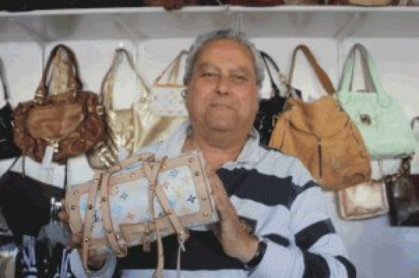 Take 2 Ladies Consignment Boutique owner David Collett shows off a Louis Vuitton bag on sale at his shop.