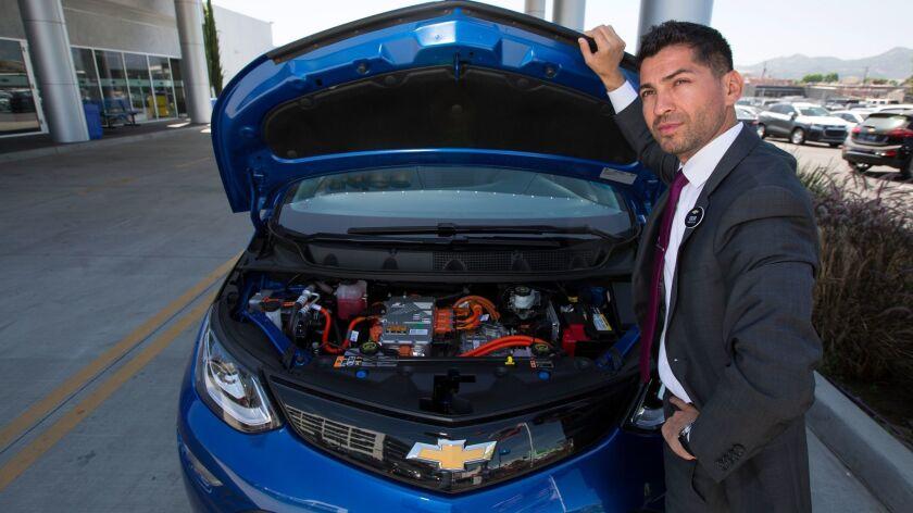 Community Chevrolet sales manager Oscar Gutierrez with a Bolt EV electric car in Burbank.