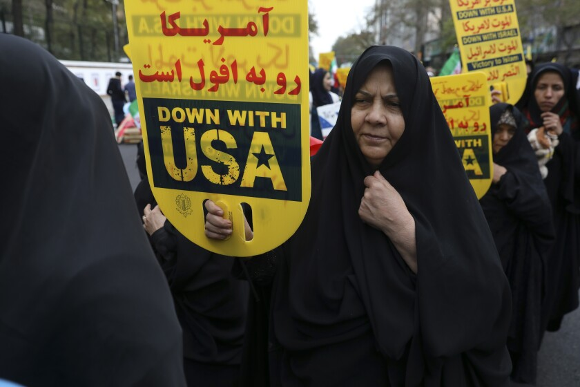 """A demonstrator holds an anti-U.S. placard during an annual rally outside the former U.S. Embassy in Tehran, Iran, Monday, Nov. 4, 2019. Reviving decades-old cries of """"Death to America,"""" Iran on Monday marked the 40th anniversary of the 1979 student takeover of the U.S. Embassy in Tehran and the 444-day hostage crisis that followed as tensions remain high over the country's collapsing nuclear deal with world powers. The Persian on top of the placard is a quotation of the Supreme Leader Ayatollah Ali Khamenei which reads: """"U.S. is on the verge of annihilation."""" (AP Photo/Vahid Salemi)"""