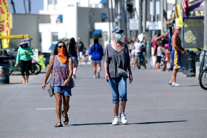 Two women wearing face coverings walk on the boardwalk in Huntington Beach on Oct. 16.