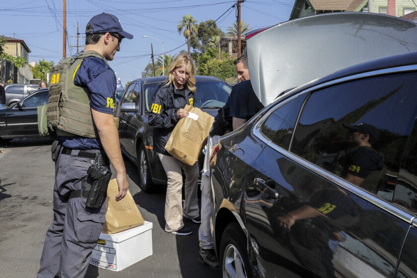 FBI agents place items taken from Councilman Jose Huizar's home in a car trunk.