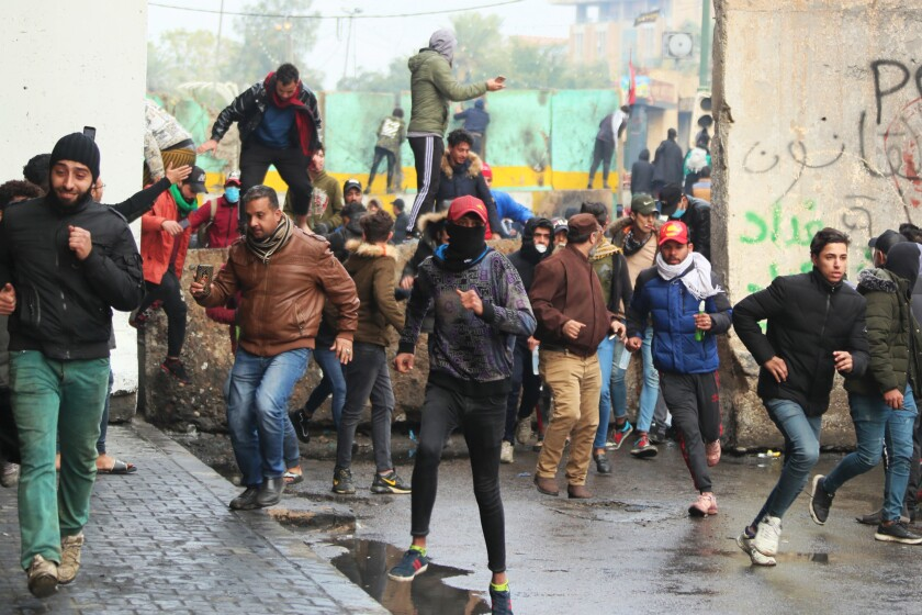 Anti-government protesters run during clashes with security forces in Baghdad on Saturday.