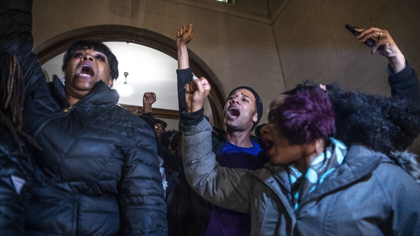Khalil Darden, 18, center, of Penn Hills, Pa., and Pennsylvania State Rep. Summer Lee, right, protest Friday at the Allegheny County Courthouse in Pittsburgh, after the not guilty verdict in the homicide trial of former Police Officer Michael Rosfeld.