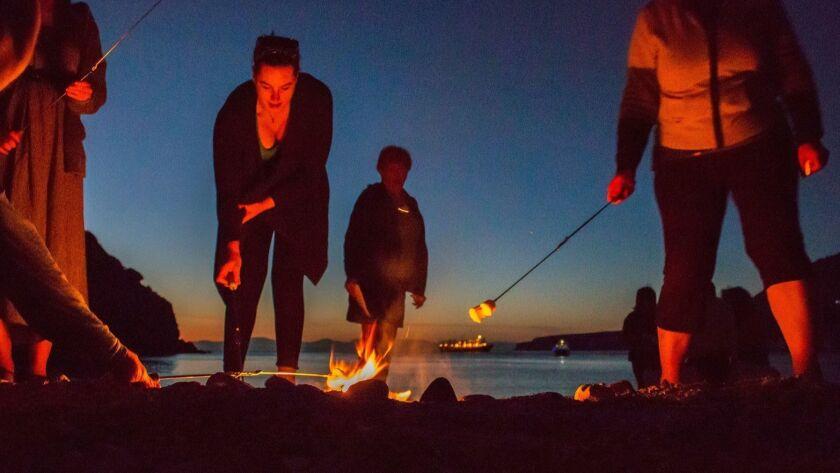 BAJA CALIFORNIA, MEXICO - Guests roasting marshmallows for s'mores on the beach of Ensenada Grande,