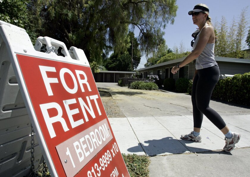 "FILE - In this July 19, 2006 file photo, a woman walks next to a ""For Rent"" sign at an apartment complex in Palo Alto, Calif. Real estate data firm Zillow reports on U.S. home rental prices in December 2014 on Friday, Jan. 23, 2015. (AP Photo/Paul Sakuma, File)"