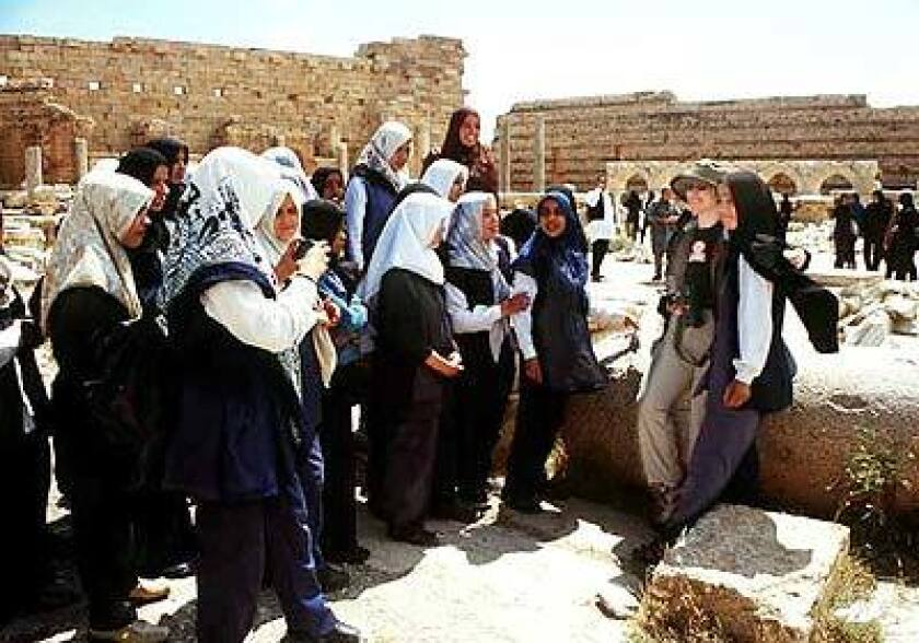Libyan schoolgirls with a Western tourist at Leptis Magna ruin, included on many cruise itineraries.