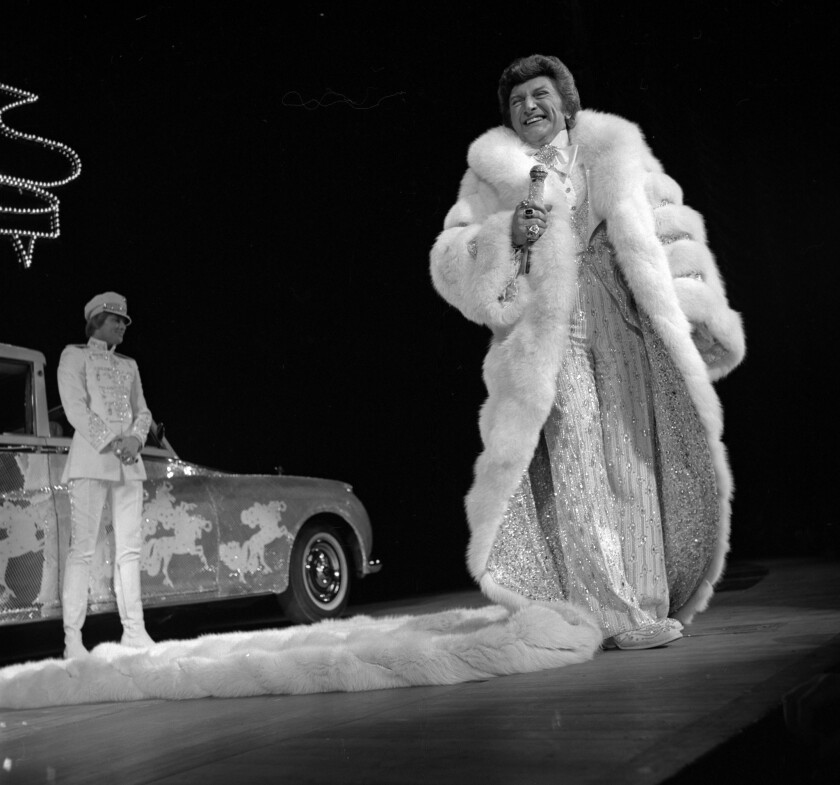 With a glittery Rolls Royce and chaffeur behind him, a mink-draped Liberace