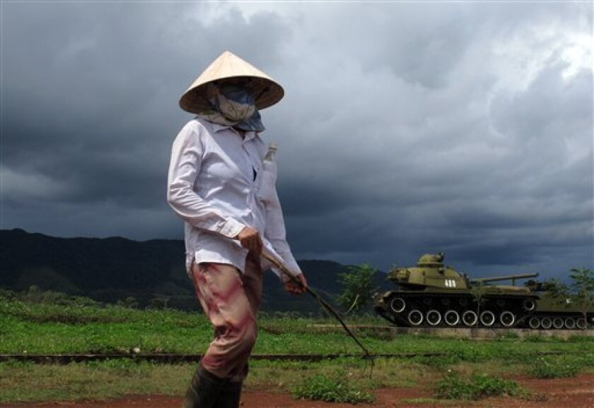 In this photo taken on Thursday, Aug. 1, 2013, a shepherdess walks in front of an American tank at a museum in Khe Sanh, Vietnam.  Aug.15 marks the 40th anniversary of the end of American bombing operations in Indochina. But in one of the grimmest legacies of the conflict, victims are still falling