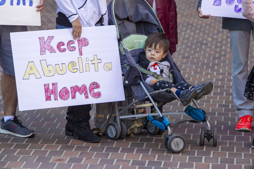 """A toddler sits in a stroller next to a woman holding a sign that says """"Keep abuelita home."""""""