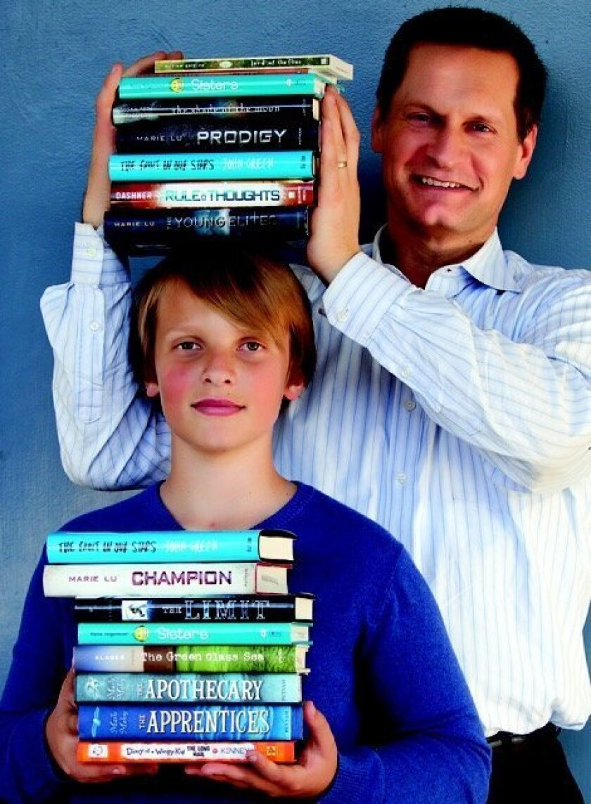 Tracy Trudeau, pictured here with his son Aiden, a sixth-grader at Muirlands Middle School, is donating $10,000 to the Muirlands Foundation over the next four years to provide new books for classrooms.
