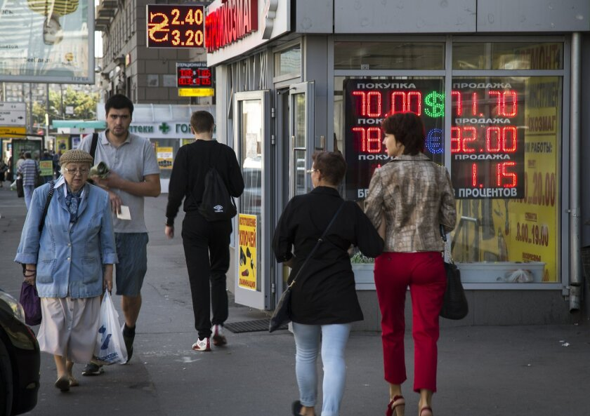 People walk past an exchange office sign showing the currency exchange rates of Ruble, Dollar, Euro and Ukrainian Hryvnia in Moscow, Russia, Monday, Aug. 24, 2015. The Russian ruble has plunged 2.3 percent to hit a seven-month low amid a further drop in oil prices, the country's key export. (AP Photo/Alexander Zemlianichenko)
