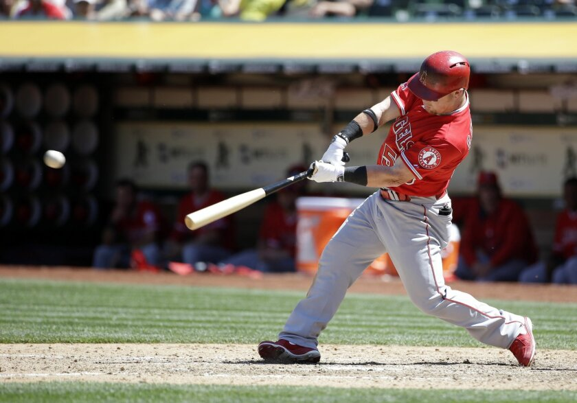 Los Angeles Angels' Kole Calhoun drives in a run with a single against the Oakland Athletics during the seventh inning of a baseball game Thursday, April 30, 2015, in Oakland, Calif. (AP Photo/Marcio Jose Sanchez)