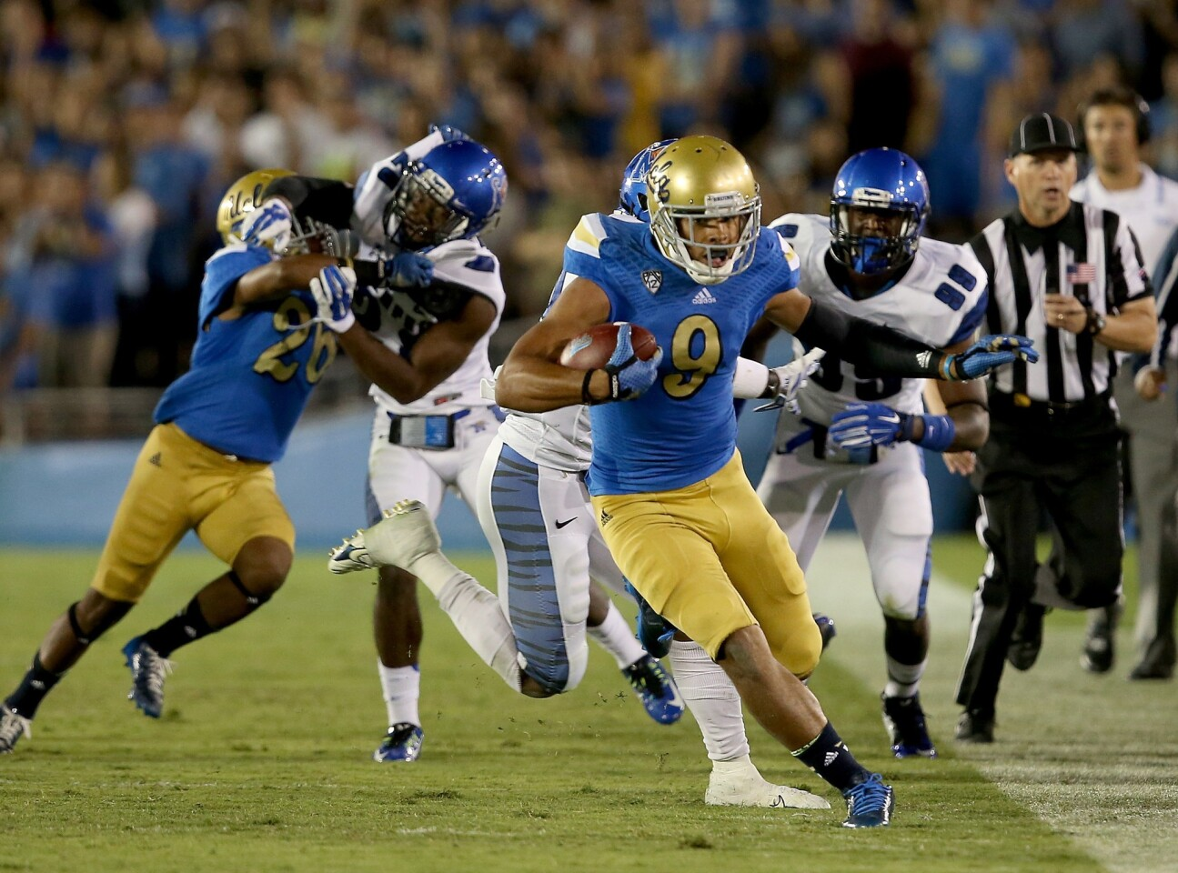 UCLA receiver Jordan Payton finds running room along the sideline after making a catch against Memphis in the third quarter Saturday at the Rose Bowl.