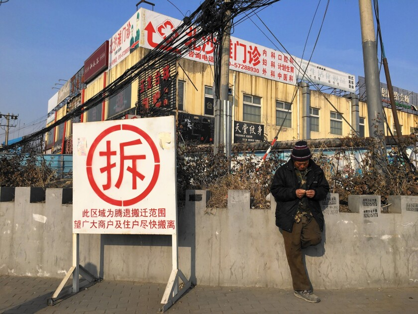 """A man in Dongsheng, one of Beijing's largest slums, stands next to a sign reading """"demolish."""" The area is set to be torn down this year, uprooting an estimated 100,000 people."""