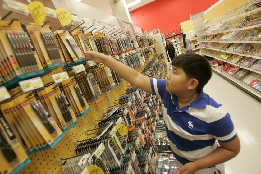 Aaron Ngo,10, of City Heights, a 5th grader at Euclid Elementary School, looks for school supplies at the Target store in Mission Valley the day before the new school year begins for San Diego Unified School District students.