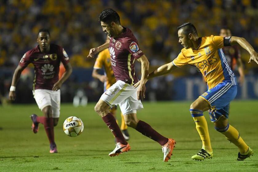 Junior Anselmo (d) de Tigres disputa el balón con Oribe Peralta (i) de Águilas del América. EFE/Archivo