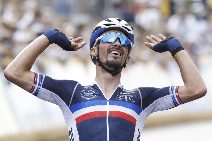 Last year's world champion Julian Alaphilippe of France celebrates crosses the finish line to claim his second title and win the men's road race of the World Road Cycling Championships with finish in Leuven, Belgium, Sunday, Sept. 26, 2021. (AP Photo/Olivier Matthys)