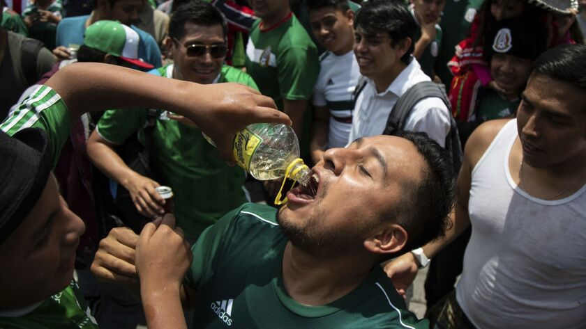 A fan has tequila poured down his throat during the celebration of Mexico's 2018 World Cup win over