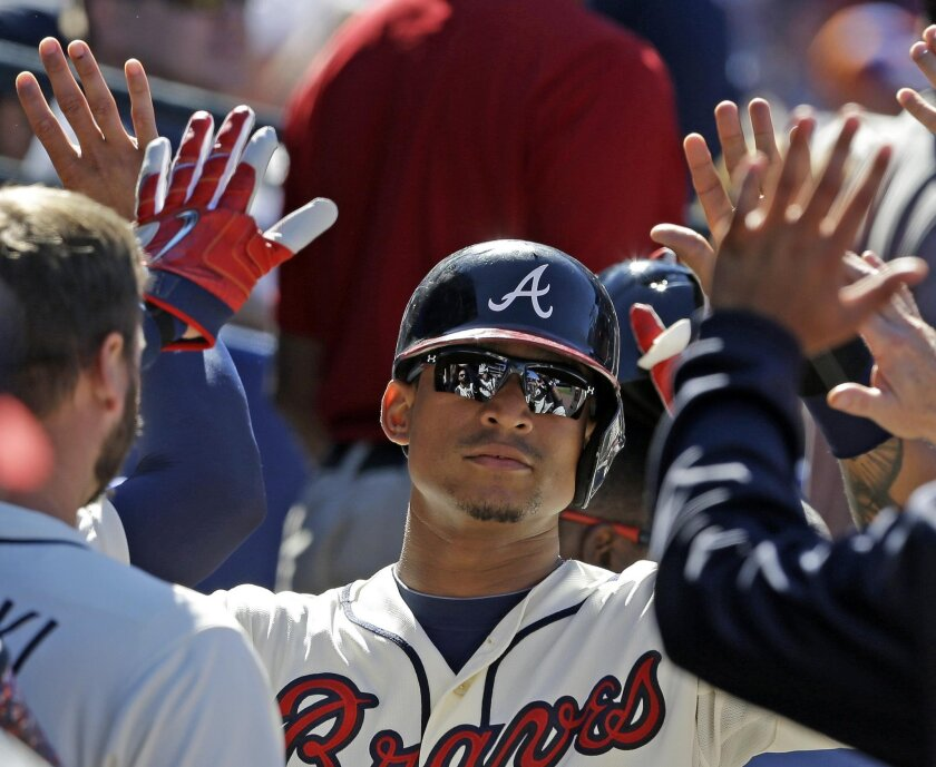 Atlanta Braves' Christian Bethancourt celebrates with teammates in the dugout after scoring a run during the eighth inning of a baseball game against the New York Mets, Sunday, Sept. 13, 2015, in Atlanta. (AP Photo/Butch Dill)