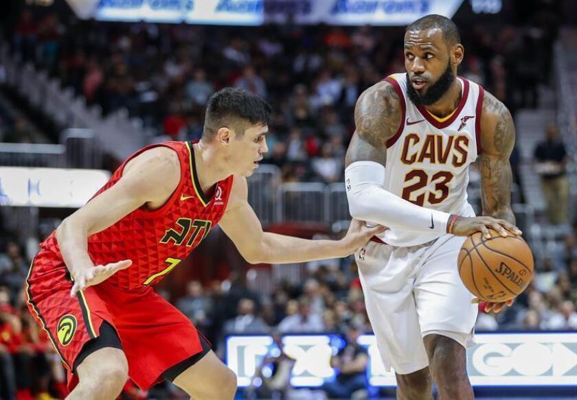 LeBron James (d), alero estrella de los Cavaliers de Cleveland, fue registrado este jueves al intentar superar la maraca de Ersan Ilyasova (i), de los Hawks de Atlanta, durante un partido de la NBA, en Atlanta (Georgia, EE.UU.). EFE