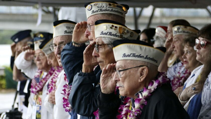Pearl Harbor survivors salute during the National Anthem at a ceremony in Pearl Harbor, Hawaii on Fr