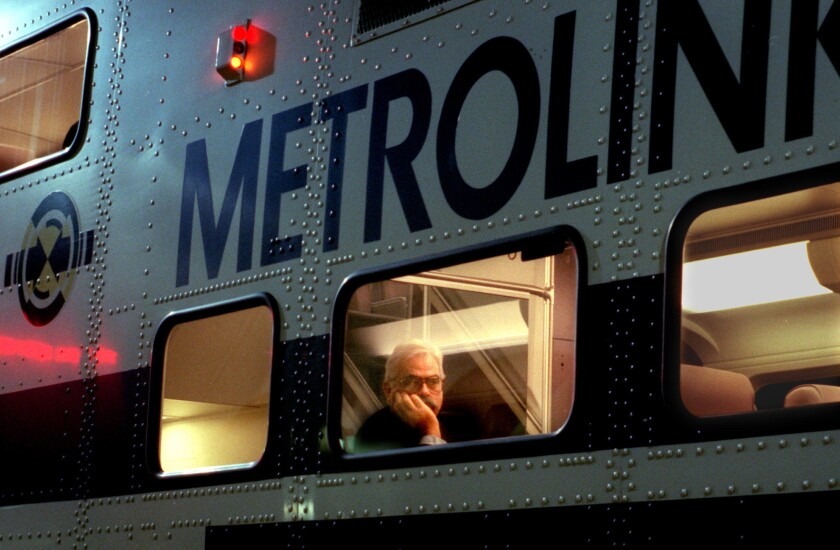 Metrolink rider looks out window as train pulls into the Santa Ana Transportation Center.