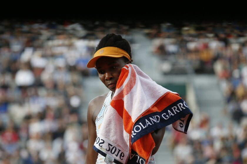 Venus Williams of the U.S wipes her face as she plays France's Alize Cornet during their third round match of the French Open tennis tournament at the Roland Garros stadium, Saturday, May 28, 2016 in Paris. (AP Photo/Alastair Grant)