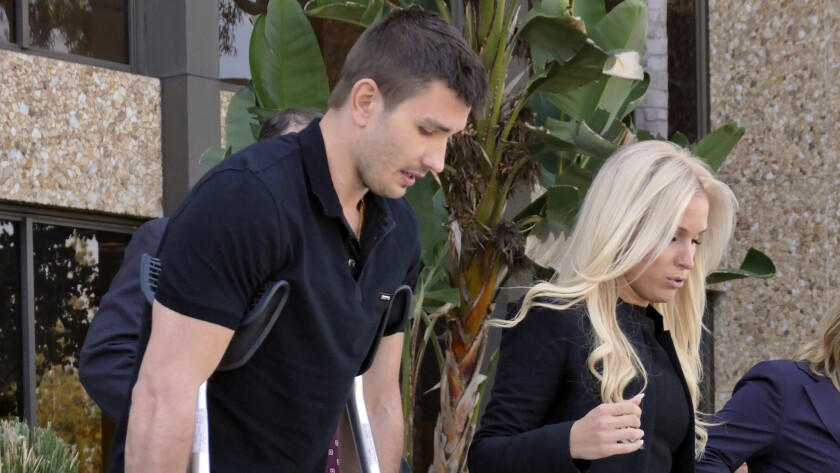 Kings defenseman Slava Voynov leaves court in Torrance on crutches with his wife, Marta Varlamova, following a judge's decision on April 1 to delay his domestic violence trial until July. Voynov ruptured his right Achilles' tendon in March.
