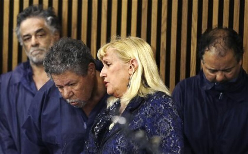 Defense attorney Kathleen DeMetz, second from right, talks with Pedro Castro as Onil Castro, left, watches and Ariel Castro, right, looks down, in Cleveland Municipal court Thursday, May 9, 2013, in Cleveland. Ariel Castro was charged with four counts of kidnapping and three counts of rape. Pedro Castro pleaded no contest to an unrelated open-container charge in court Monday. Two unrelated misdemeanor charges against Onil Castro were dropped. Police announced on Thursday afternoon that 54-ye