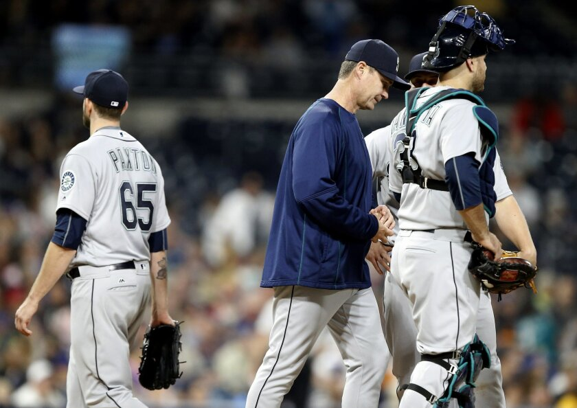 Seattle Mariners starting pitcher James Paxton walks away from the mound after being taken out by manager Scott Servais, center, during the fourth inning of a baseball game against the San Diego Padres in San Diego, Wednesday, June 1, 2016. (AP Photo/Alex Gallardo)