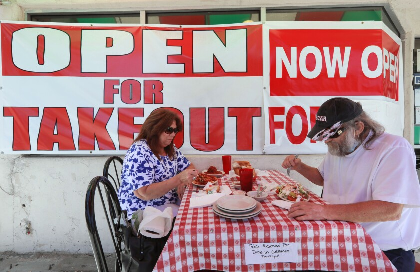 Kim and Dave Mason enjoy their lunch on the sidewalk in front of Filippi's Pizza on Grand Avenue in downtown Escondido.