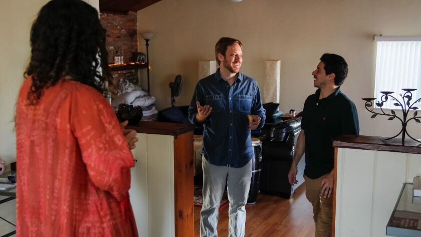 Moishe House residents Chelsea Bradford-Hall, left, and Moses Wosk, right, chat with Rabbi Brad Greenstein, who is the senior director of Jewish learning for Moishe House.