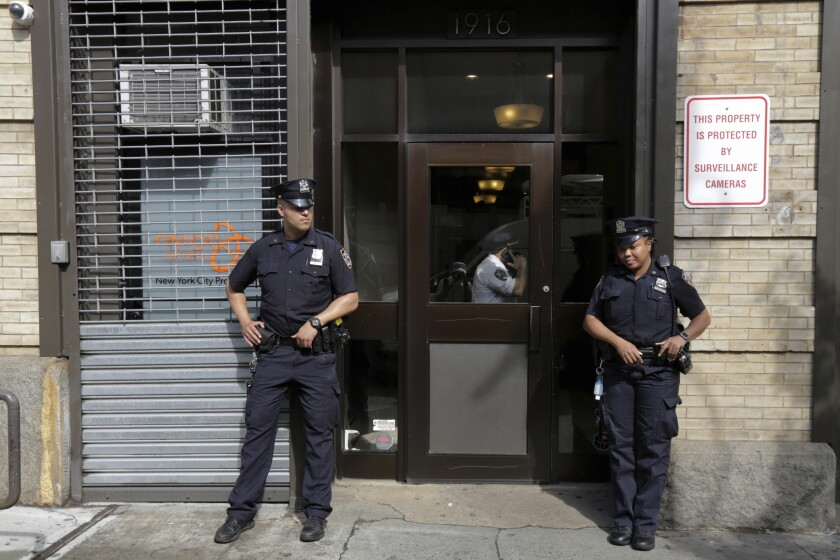 Police stand outside an office for the Cayuga Centers in New York.