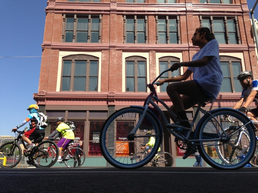 Cyclists pedal near the downtown start of the CicLAvia course.