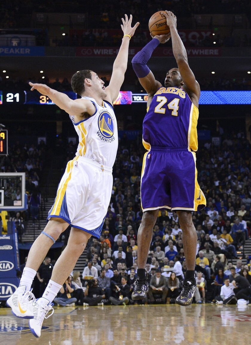 Lakers guard Kobe Bryant shoots over Warriors guard Klay Thompson.