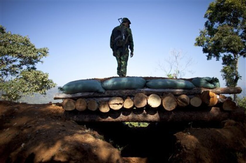 In this Jan. 31, 2013 photo, a Kachin Independence Army soldier stands on top of a bunker at an outpost on the Law Hpyu hilltop, one of the last hilltop outposts defending Laiza, where the guerrilla group's headquarters are located, in northern Myanmar's Kachin-controlled region. Kachin state is ho