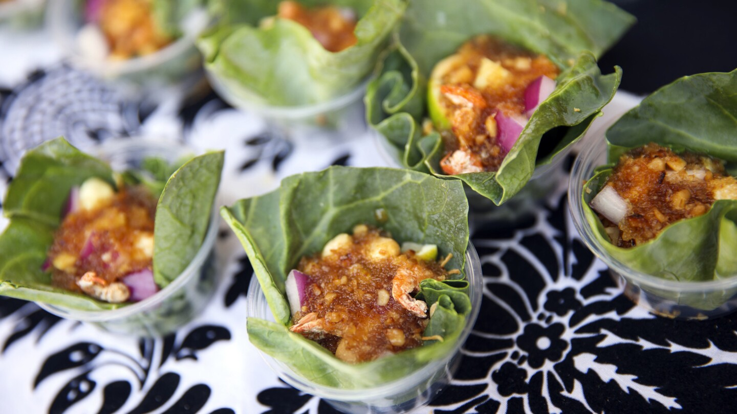 Miang Kham, a traditional Thai snack with shrimp, shallots, red onion, chili peppers, ginger, garlic, lime, roasted coconut, peanuts in a Chinese broccoli leaf wrapper from Lum-Ka-Naad.