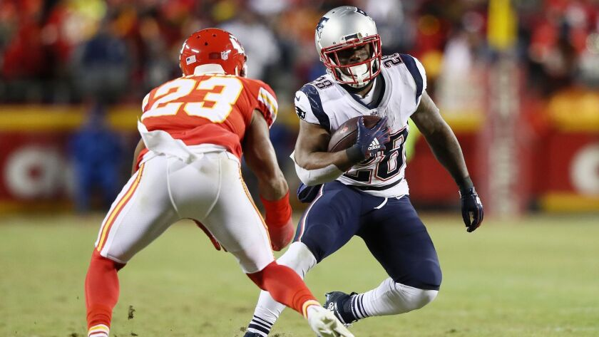 New England Patriots running back James White runs with the ball in front of Kansas City Chiefs defensive back Kendall Fuller during the AFC championship game.