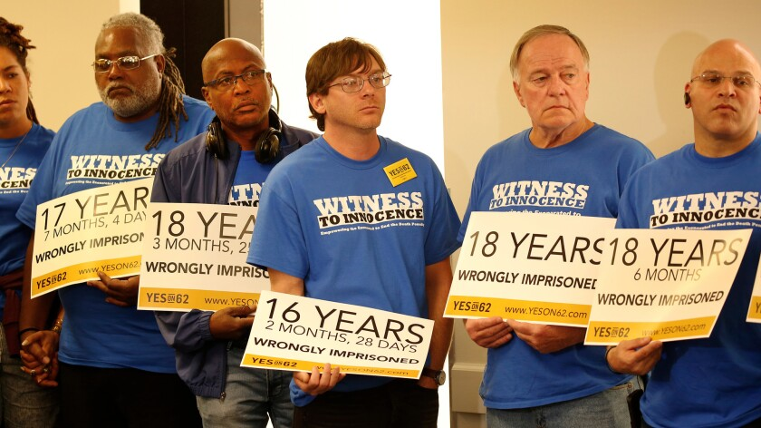 Death row exonerees from across the nation hold signs showing the number of years they were wrongly imprisoned as they listen to Mike Farrell at a Prop. 62 campaign event.