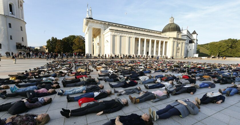 Hundreds of activists lay down at Cathedral square in Vilnius, Lithuania, Tuesday, Sept. 22, 2015. The protest action is aimed to bring public and officials attention to the issue of people committing suicide. (AP Photo/Mindaugas Kulbis)