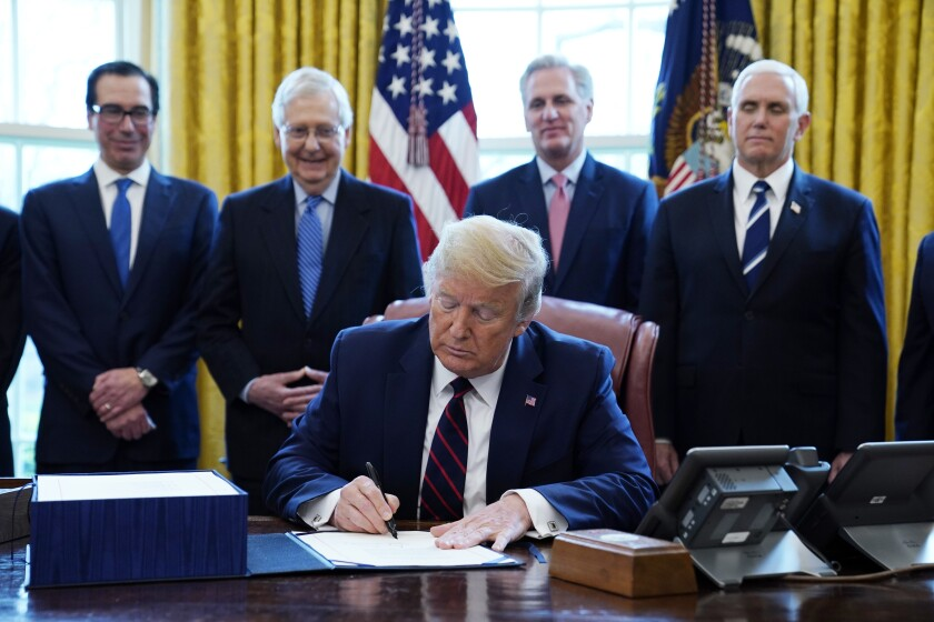 President Trump signs the coronavirus stimulus relief package at the White House.
