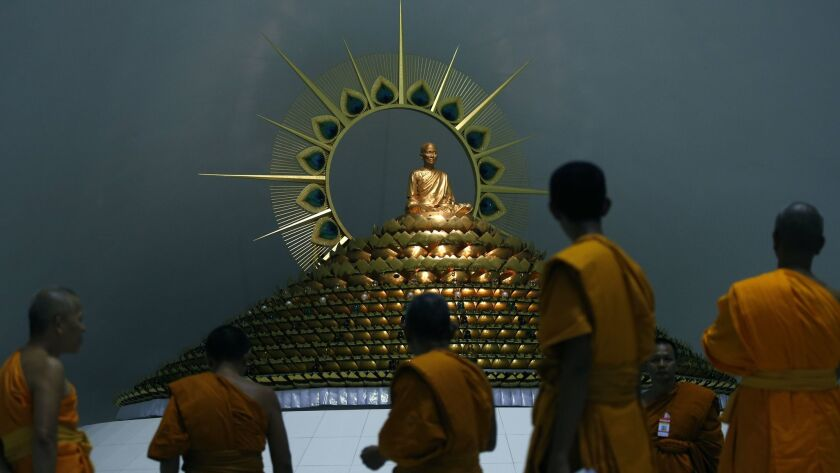 Buddhist monks walk together during a search inside Wat Phra Dhammakaya Temple in Pathum Thani province, on the outskirts of Bangkok.