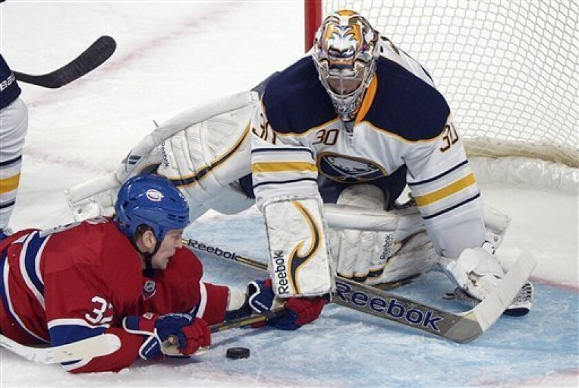 Montreal Canadiens' Travis Moen (32) slides in on Buffalo Sabres' goaltender Ryan Miller during the second period of  an NHL hockey game in Montreal, Saturday ,Feb. 2, 2013. (AP Photo/The Canadian Press, Graham Hughes)