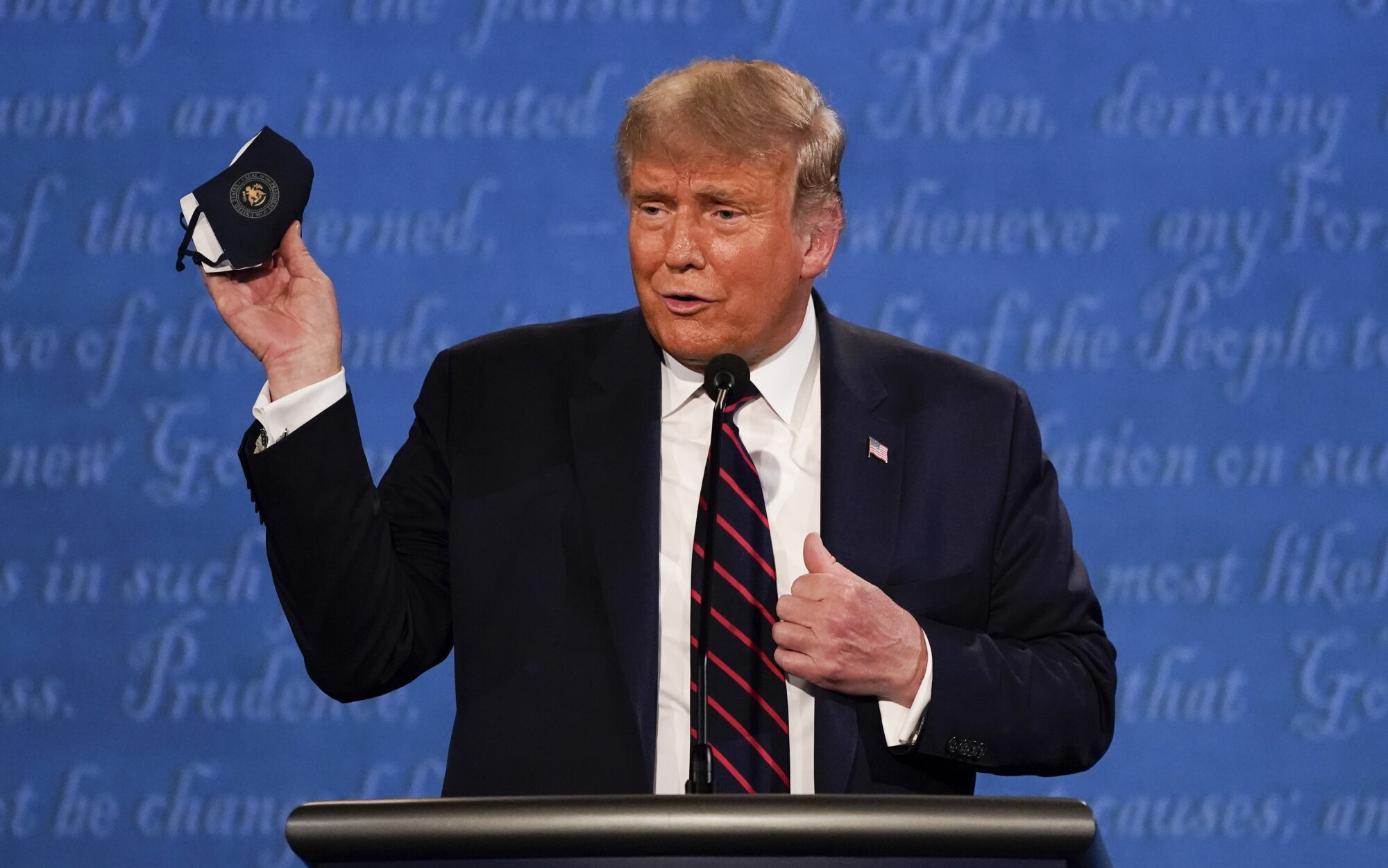 President Trump holds up his face mask during Tuesday's debate in Cleveland